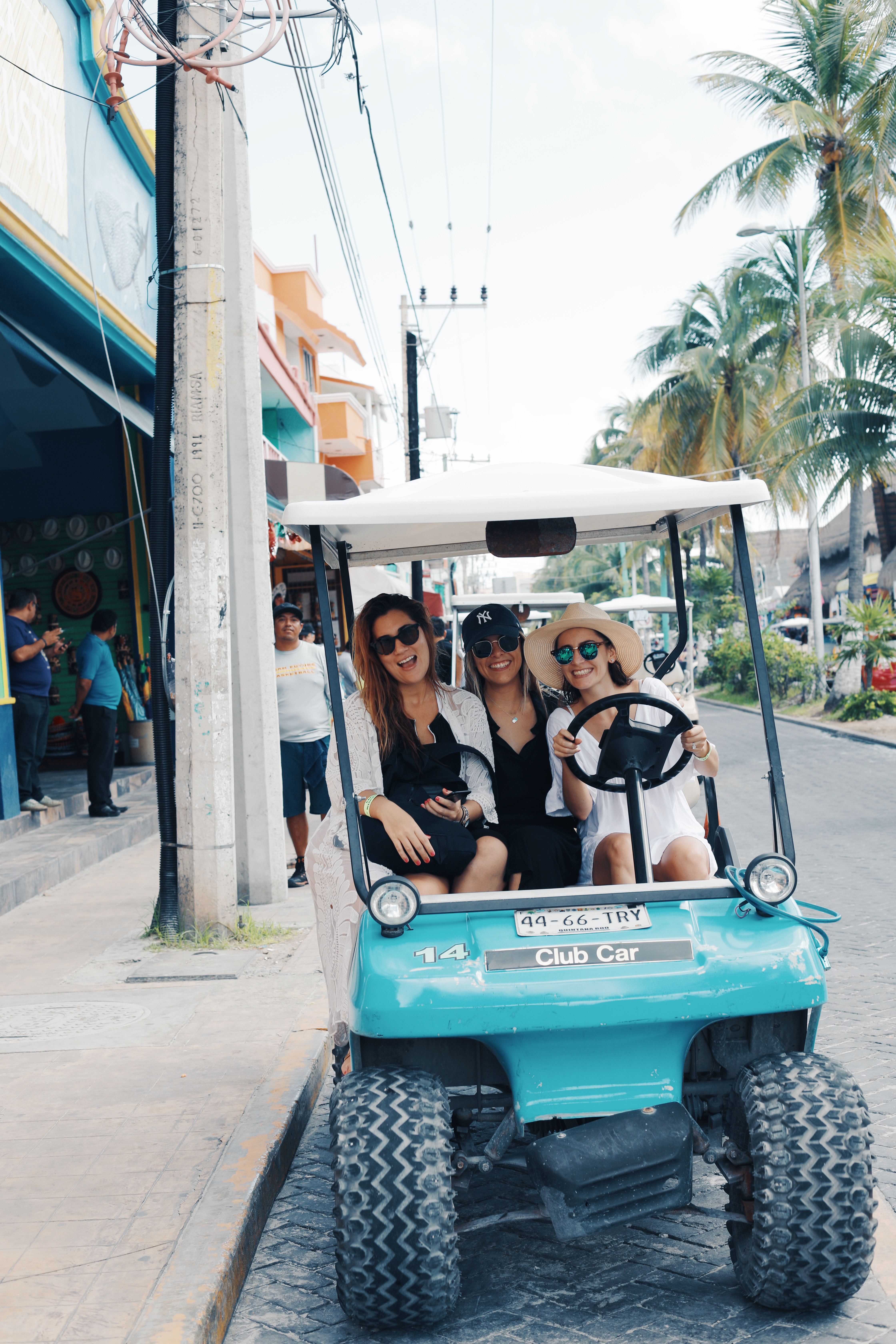 3 Girls driving a golf cart on the main road of Isla Mujeres Mexico