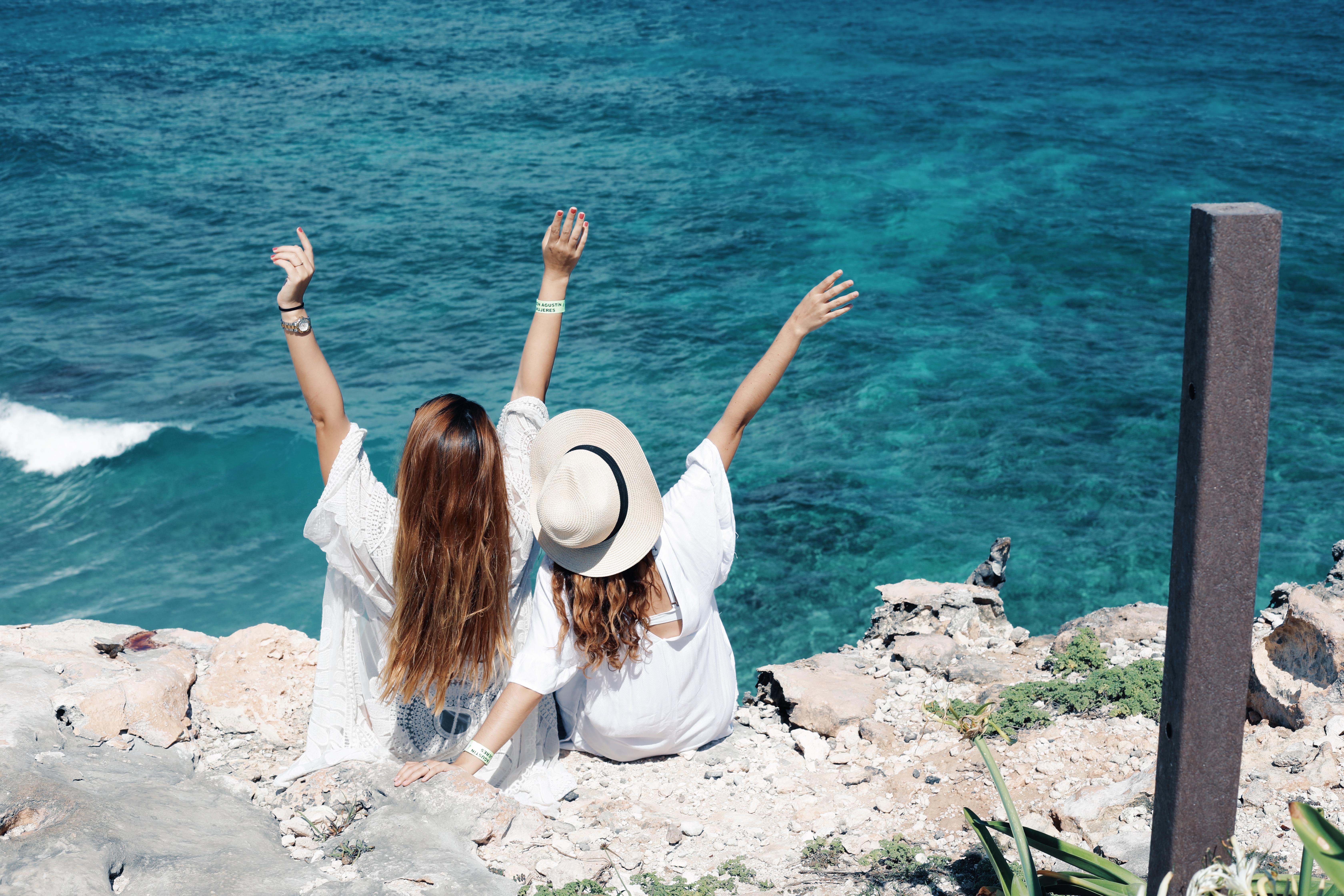 2 Girls watching the ocean sitting on the rocks of punta sur Isla Mujeres