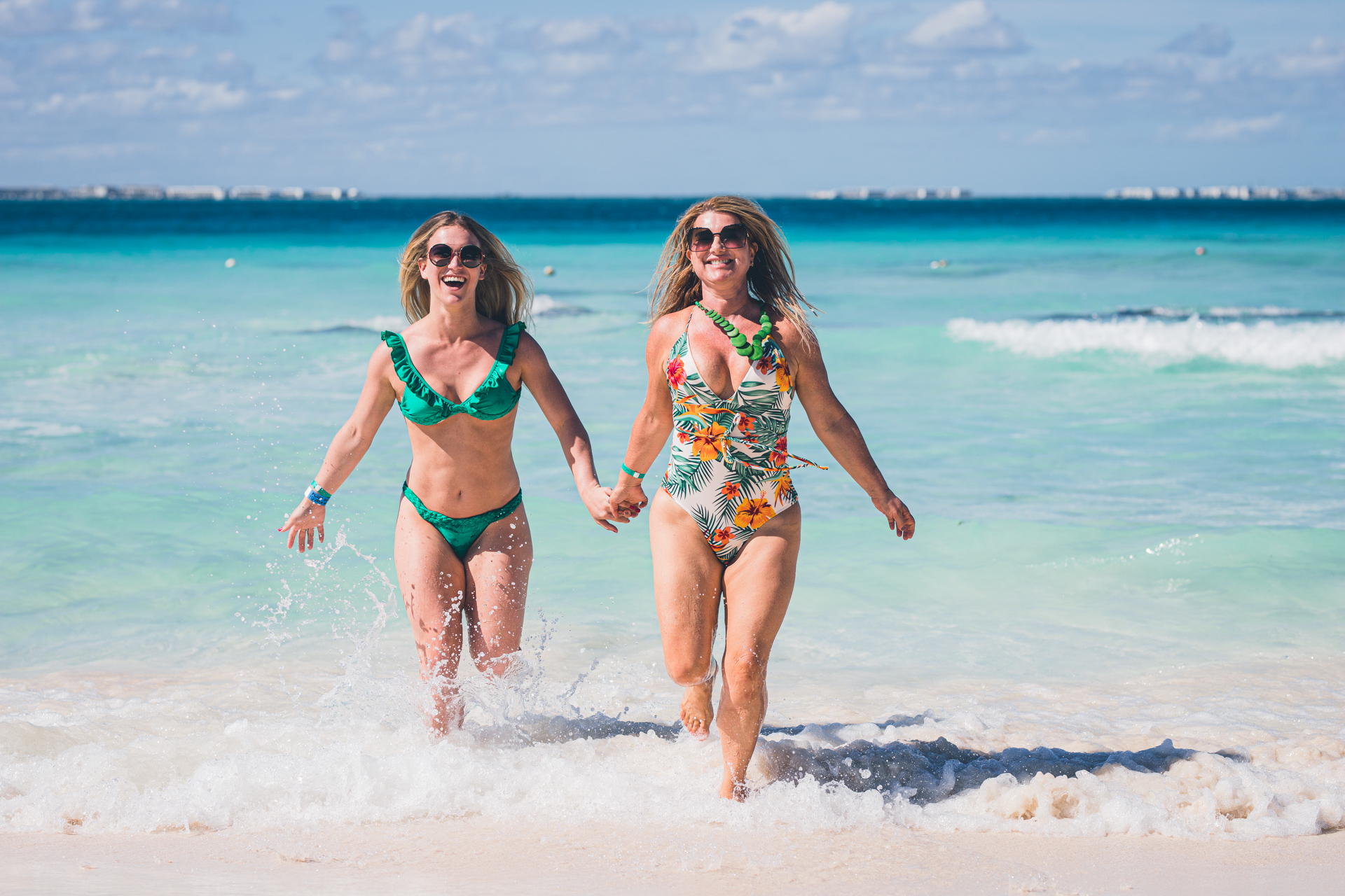Daughter and mom grabbing hands and smiling in Playa Norte Beach at Isla Mujeres
